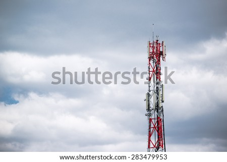 GSM Antenna Transmitters on Red and White Industrial Communication Tower - stock photo