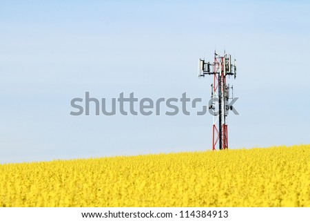 Gsm transmitter on a blooming field - stock photo