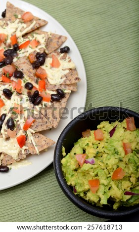 Guacamole and vegan nachos with black beans - stock photo