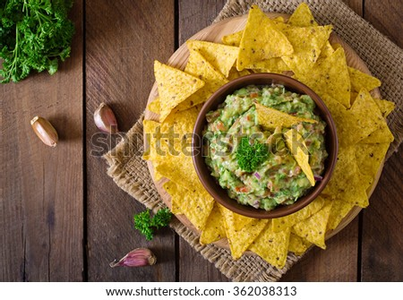 Guacamole avocado, lime, tomato, onion and cilantro, served with nachos - Traditional Mexican snack. Top view - stock photo