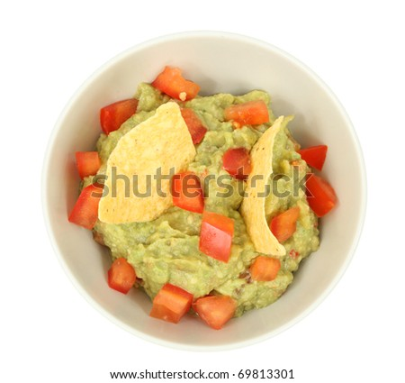 Guacamole dip with tortilla chips isolated over white background - stock photo
