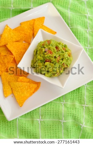 Guacamole made from avocado, lime, tomato, red onion and cilantro served with tortilla chips. - stock photo