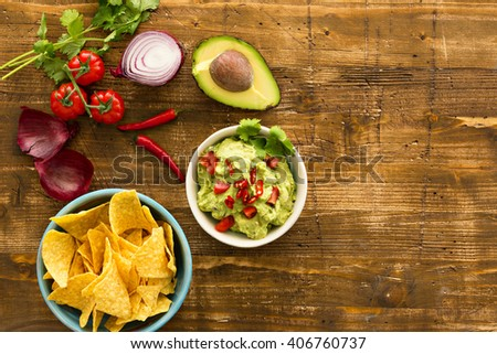 Guacamole with avocado and tomatoes mexican food. wooden background - stock photo