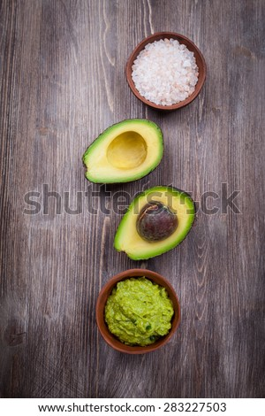 Guacamole with avocado on wooden table  - stock photo