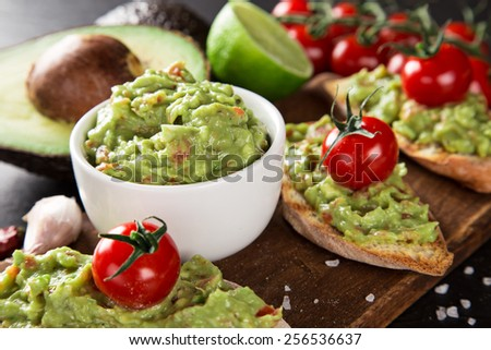 Guacamole with bread and avocado on stone background - stock photo