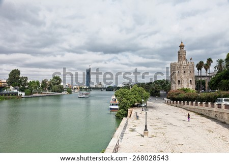 Guadalquivir River Embankment and Gold tower (Torre del Oro) in Seville, Spain - stock photo