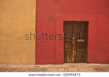 GUANAJUATO, MEXICO - September 24, 2015: Street view of wall and doors in colonial San Miguel de Allende, the UNESCO World Heritage Site. 16th century old buildings & streets are preserved. - stock photo