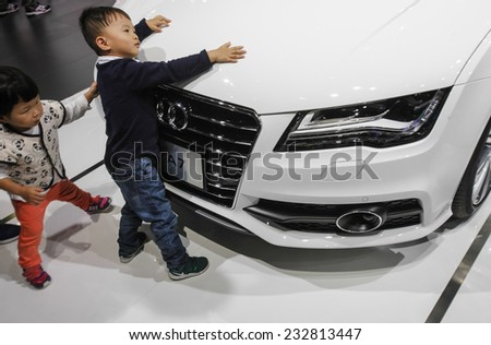 GUANGZHOU, CHINA - NOV. 20. 2014: Children play on Audi stand near Audi A7 car on the 12th China International Automobile Exhibition in Guangzhou. - stock photo