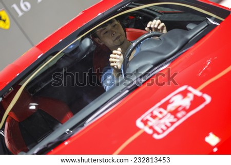 GUANGZHOU, CHINA - NOV. 20. 2014: Man seating in Ferrary car on the 12th China International Automobile Exhibition in Guangzhou, Guangdong province. - stock photo