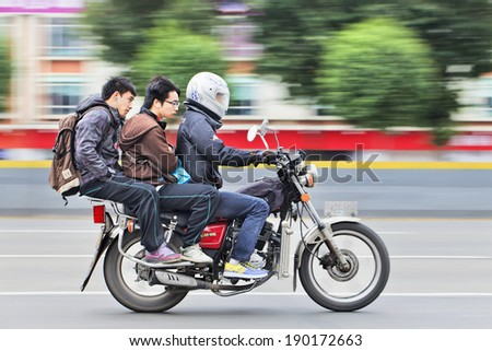 GUANGZHOU-FEB. 22, 2012. Dalong motorcycle taxi with two passengers. Although the Guangzhou municipal government has banned motorcycle taxis for safety reasons it i??s still a popular transport mode. - stock photo