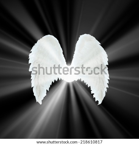 Guardian Angel   white wings over black background with light. Religion and spiritual concept  - stock photo