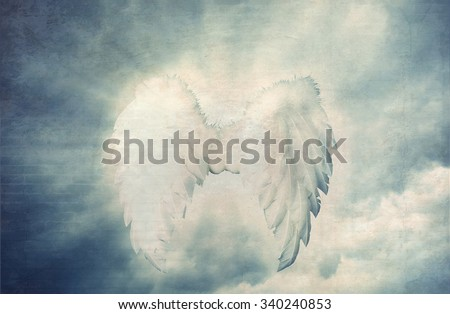 Guardian Angel white wings over dramatic grey with light. Religion and spiritual concept - stock photo