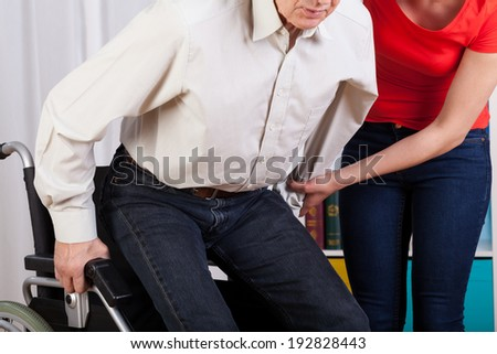 Guardian helping her disabled patient with sitting down - stock photo