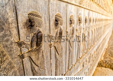 Guardians also known as the Immortals holding a spear, relief detail on the stairway facade of the Apadana at the old city Persepolis. - stock photo