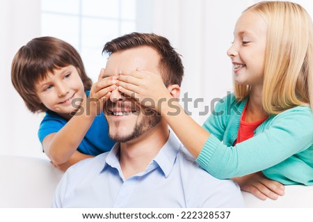Guess who? Two playful kids covering eyes of their cheerful father and smiling  - stock photo