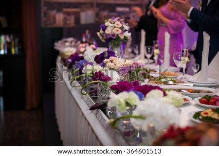 Guests at elegantly served and catered wedding reception flowers closeup - stock photo