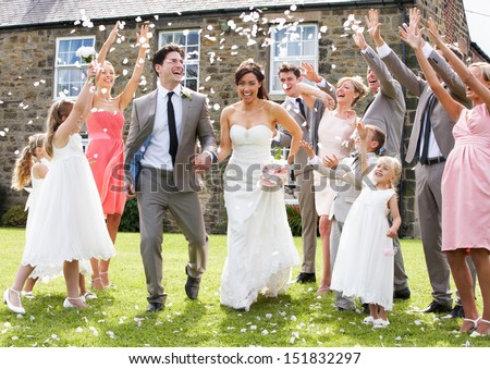 Guests Throwing Confetti Over Bride And Groom - stock photo