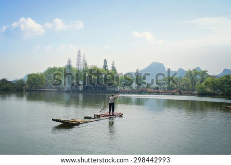 GUILIN CHINA - APR 03: The old lady paddling her boat on the west bank of the Li Jiang River. Taken on Apr 03, 2015, Guilin, China - stock photo