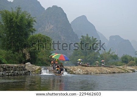 Guilin, China - 14 October 2014 - Tourists ride on a bamboo raft along the Yulong river, in Guilin China. Yangshuo County, in the northeast of Guangxi, China is one of the tourist spots in Guilin. - stock photo