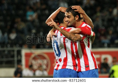 GUIMARAES, PORTUGAL - AUGUST 25: Adrian Lopes(R) from At.Madrid(ESP) celebrates with his teammates another goal at the 2011\2012 UEFA Europa League on August 25, 2011 in Guimaraes, Portugal - stock photo