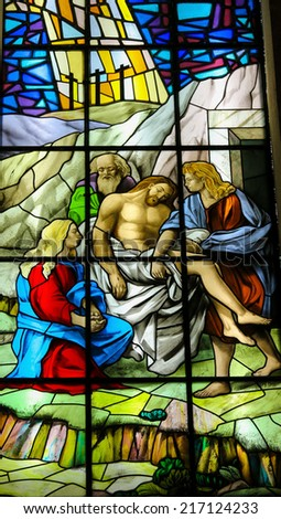 GUIMARAES, PORTUGAL - AUGUST 7, 2014: Stained glass window depicting Jesus carried to His Tomb in the Santos Passos church in Guimaraes, Portugal. - stock photo