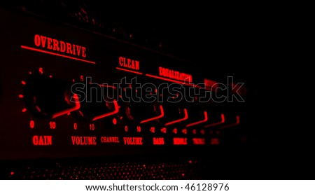 guitar amplifier control panel in red light, black background - stock photo