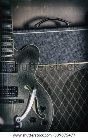Guitar and Amplifier Vintage Close Up. Guitar and amplifier, shot with spot lighting and edited with a vintage filter. - stock photo