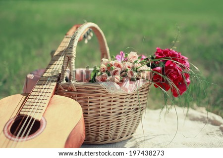 Guitar, basket and bouquet of flowers. Vintage tender background. Romance, love, date, Valentine's day - concept - stock photo