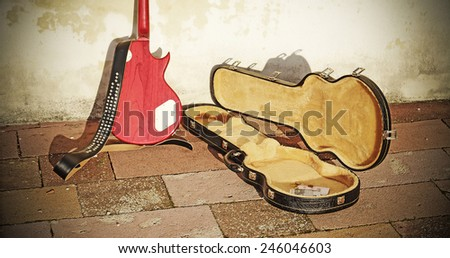 guitar case with coins and bills in vintage tone - stock photo