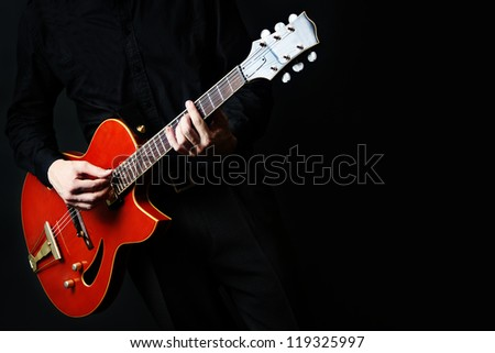 Guitar electric Guitarist playing red music instrument in hands closeup on black - stock photo