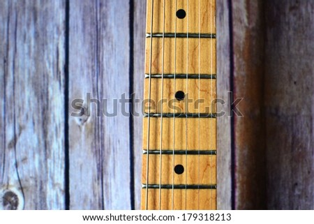 Guitar fretboard against wood panel background. - stock photo