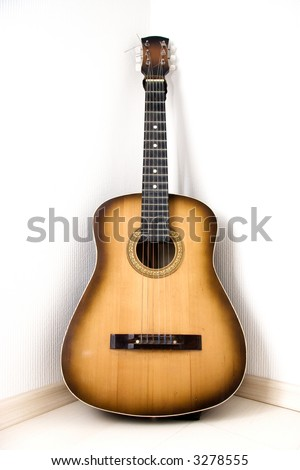 Guitar in a corner of room. - stock photo