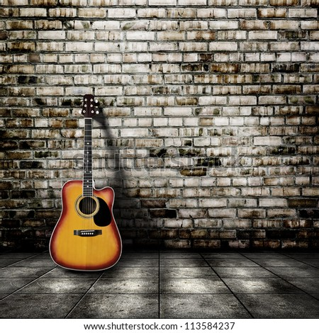 Guitar in blank empty room with brick wall background - stock photo