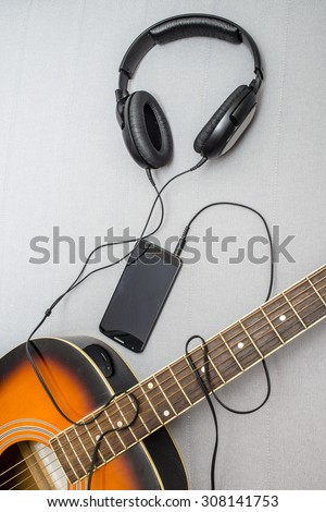 guitar lying on the sofa and lie next to the headphones connected to a mobile phone, the wire from which form the silhouette of a guitarist playing - stock photo