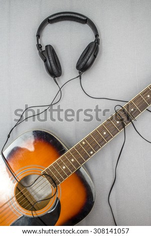 guitar lying on the sofa and lie next to the headphones, the wire from which form the silhouette of a guitarist playing - stock photo