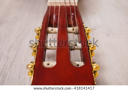 guitar neck on a wooden background, musical instrument, fretboard, stringed musical instruments, guitar details close up, solo instrument, blues, country, flamenco, rock, metal, jazz     - stock photo
