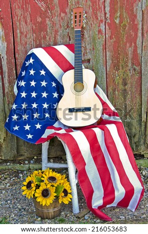guitar on an American flag with sunflower basket by old weathered barn - stock photo