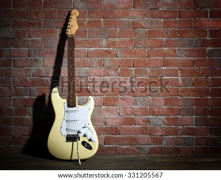Guitar on brick wall background - stock photo