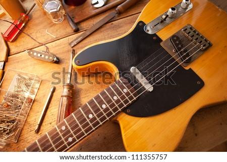 Guitar on guitar repair desk. Vintage electric guitar on a guitar repair work shop. Single cutaway solid body guitar, amber color. - stock photo