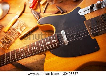 Guitar on guitar repair desk. Vintage electric guitar on a guitar repair work shop. Single cutaway electric guitar, amber color. - stock photo