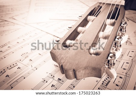guitar on music sheet , headstock closeup old film processed - stock photo