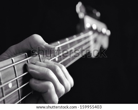 Guitar player fretting notes on a bass against black background. - stock photo
