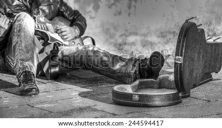 guitar player in the street with an open guitar case in black and white - stock photo