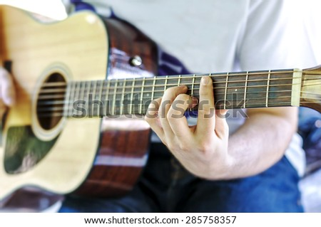 Guitar player playing song outdoor in park - stock photo