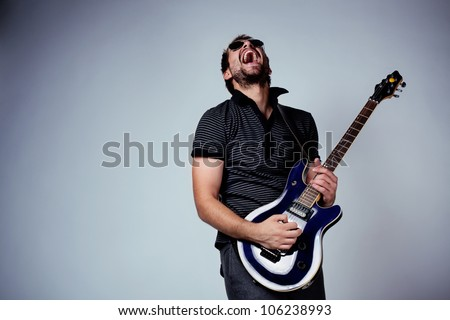 Guitar player. Rockstar playing on guitar. - stock photo