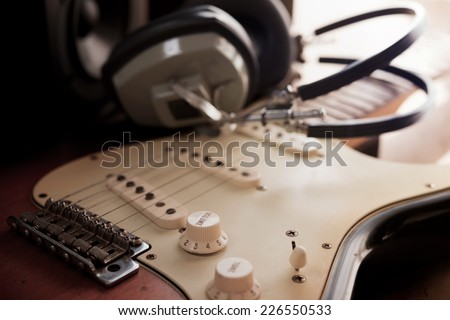 Guitar recording scene. An electric guitar, and a professional grade headphones.  - stock photo