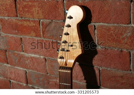 Guitar's fingerboard on brick wall background - stock photo