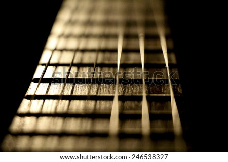 Guitar strings. Closeup of music instrument isolated on black background - stock photo