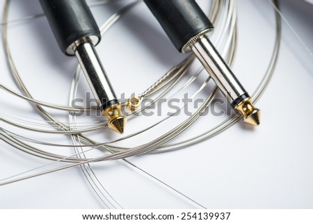Guitar strings with cable and jacks - stock photo