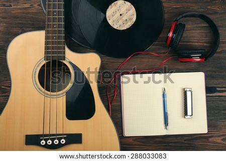 Guitar with vinyl records and notebook on wooden table close up - stock photo